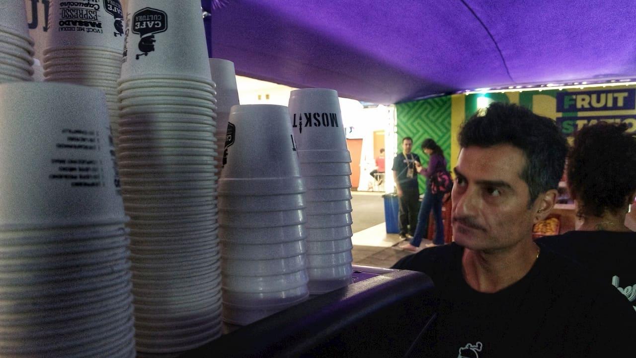 Homem olhando pilha de copos