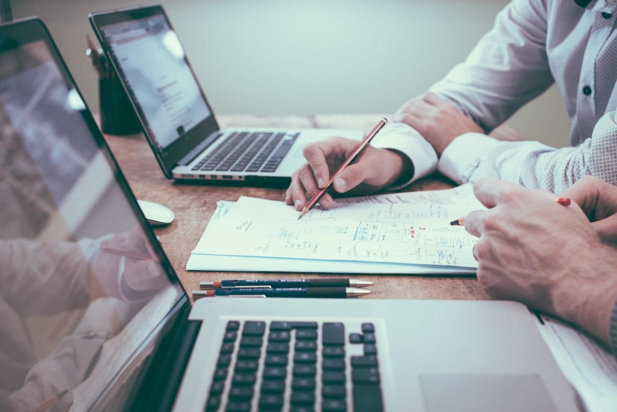 homem escrevendo no notebook em um escritorio