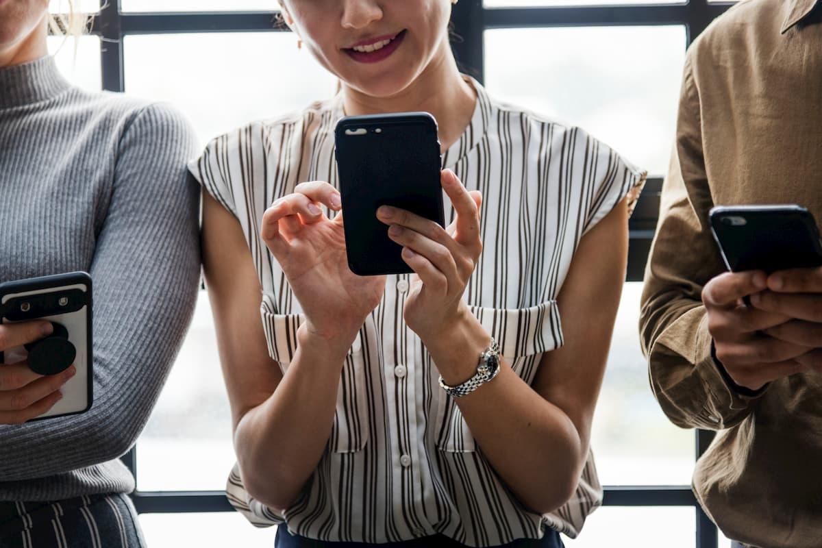 mulher usando celular ambiente empresarial